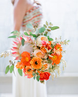 Bright orange ranunculus and king protea wedding bouquet