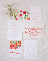 White wedding invitations with coral lettering and bright coral watercolor flowers