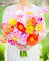 Bride Holding Bright Yellow, Pink, and Orange Bouquet