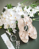 Trailing white orchid wedding bouquet beside blush wedding shoes