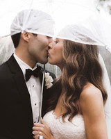 rainy wedding couple kiss under sheer umbrella