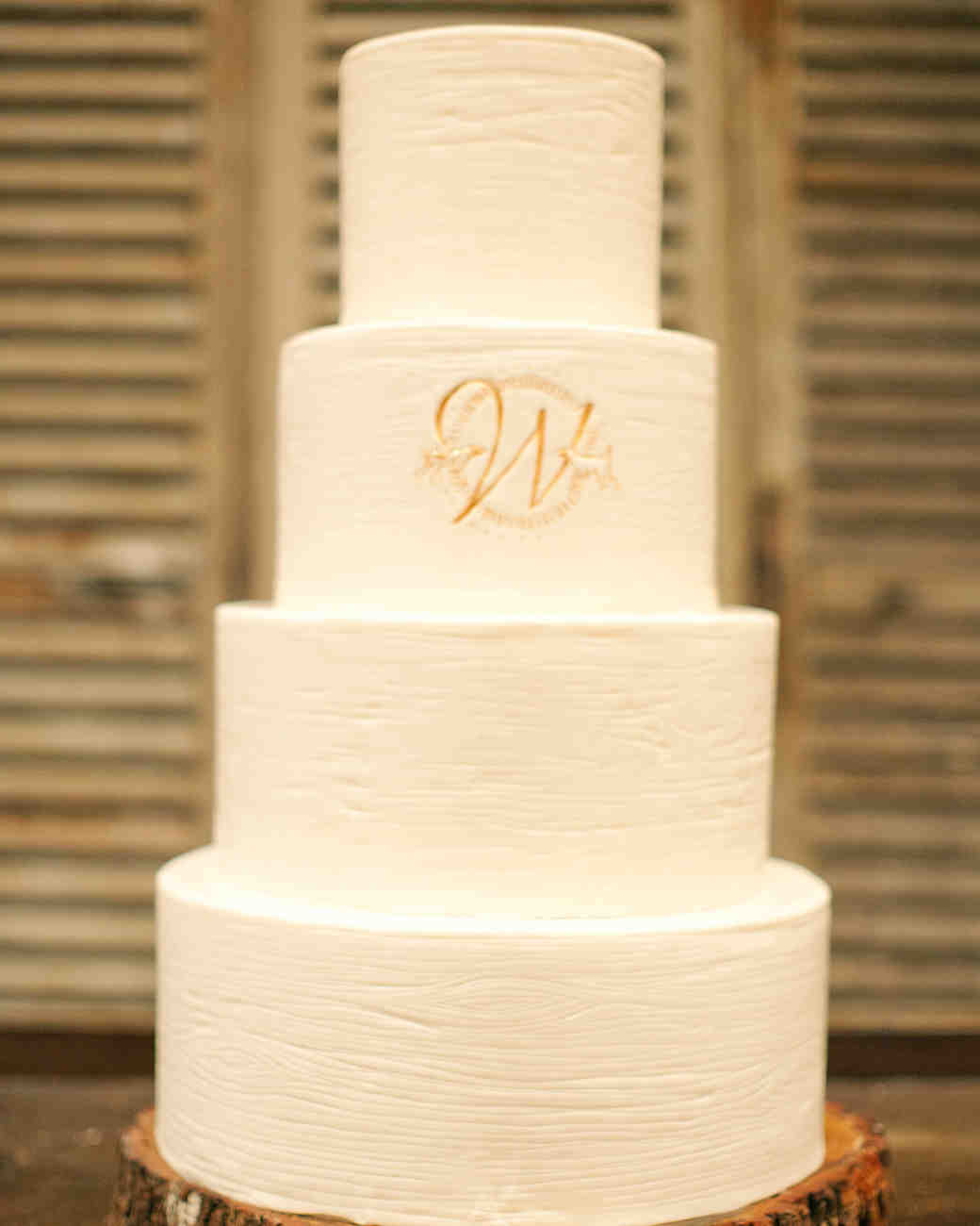 White Four-Tiered Wedding Cake with Gold Monogram