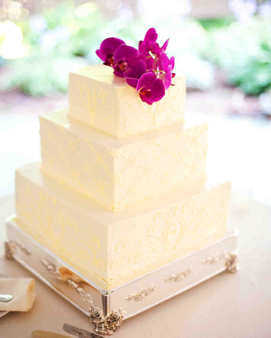 Three-Tiered White Wedding Cake with Patterned Piping and Orchid Topper