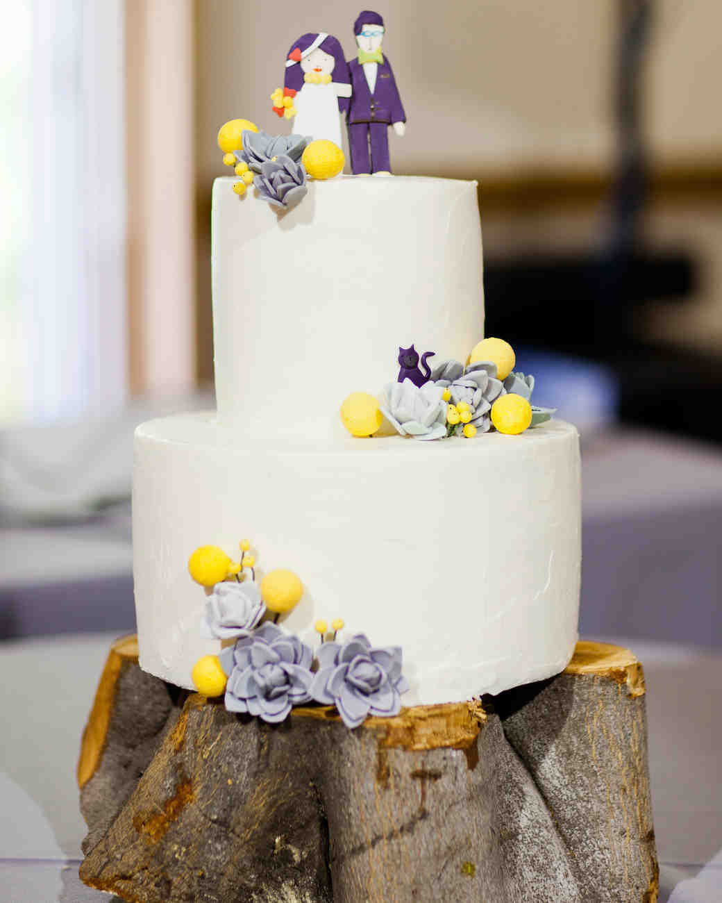 Two-Tiered White Wedding Cake with Purple and Yellow Candy Topper and Accents