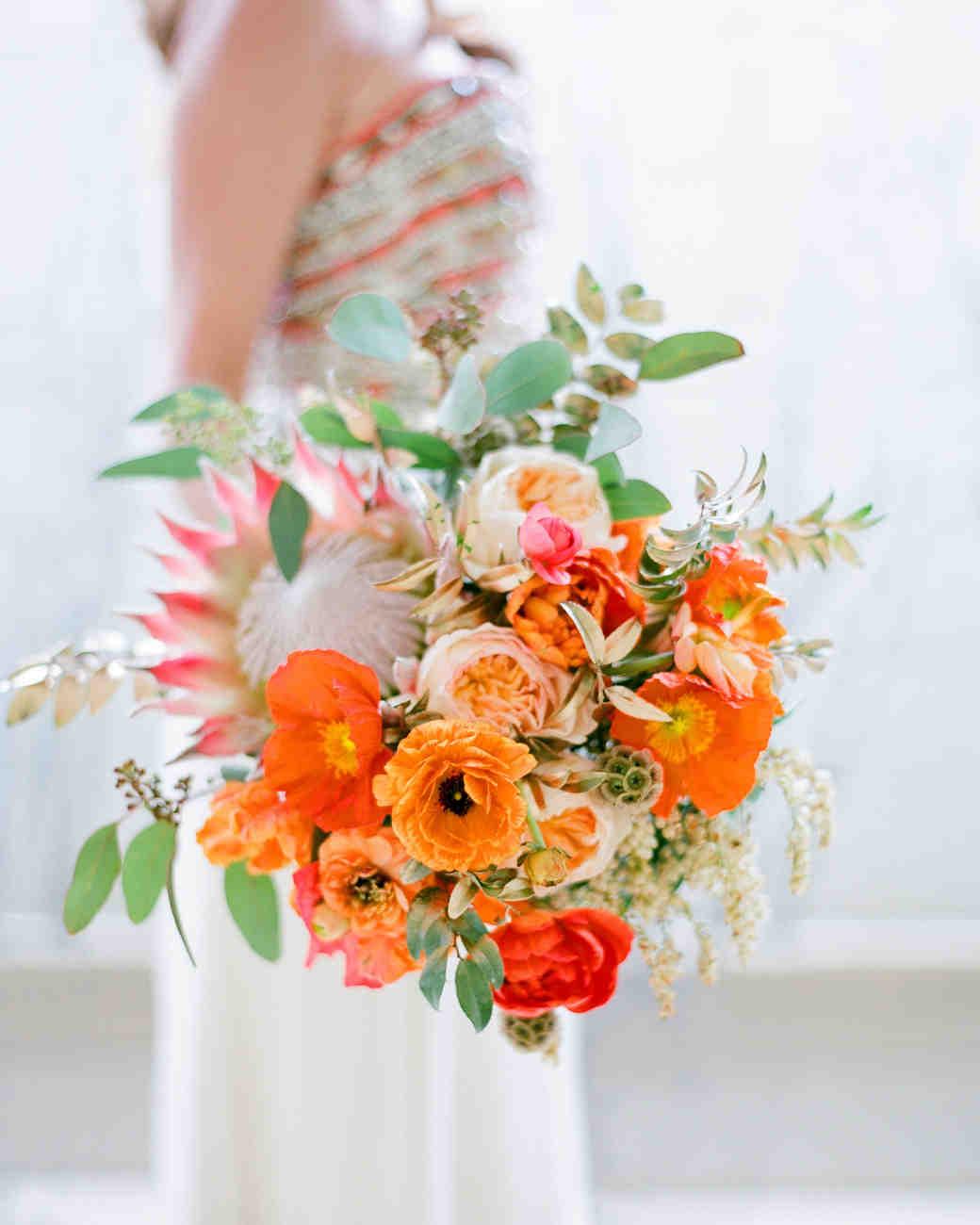Bright orange ranunculus and king protea wedding bouquet