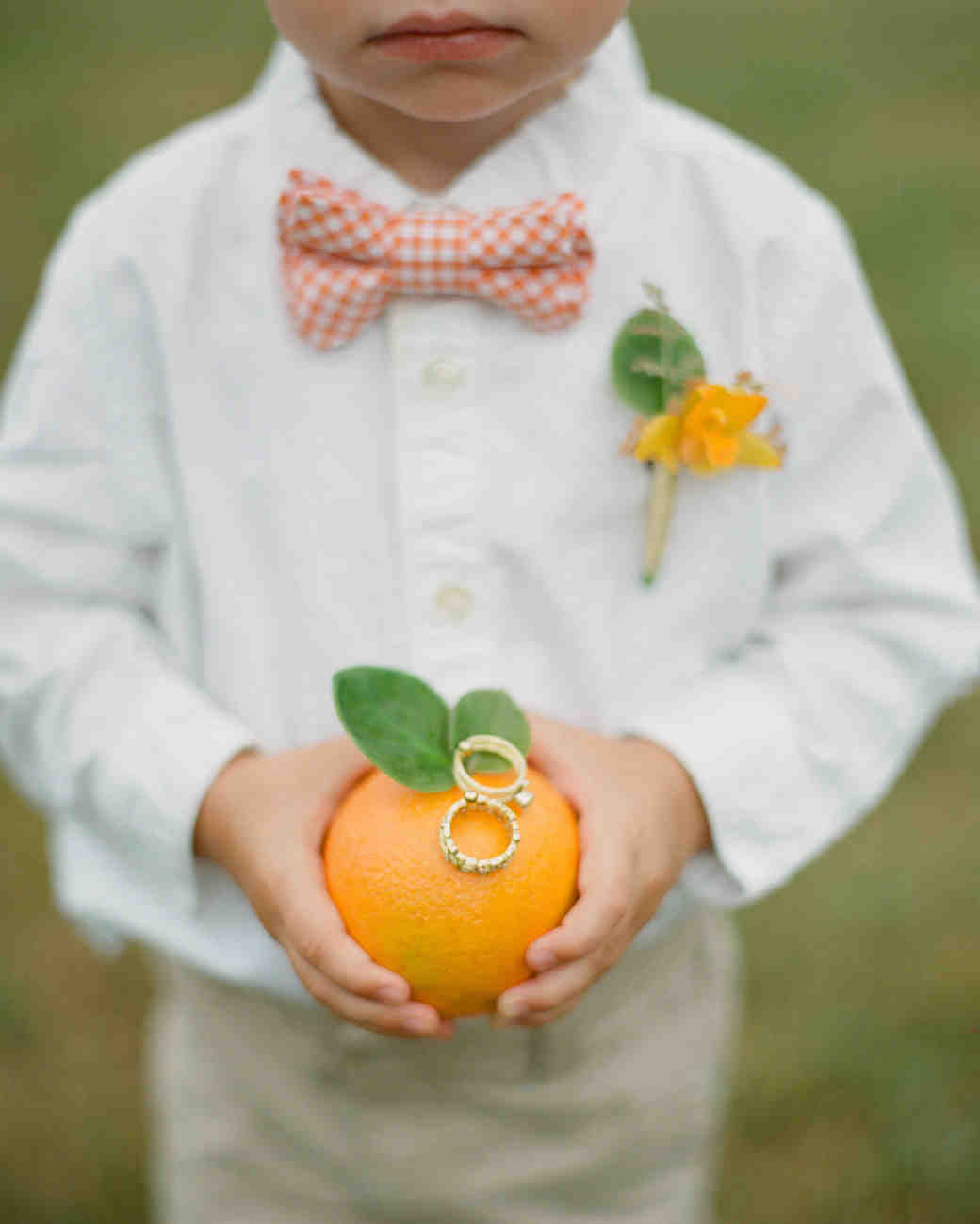 ring bearer holding rings on orange