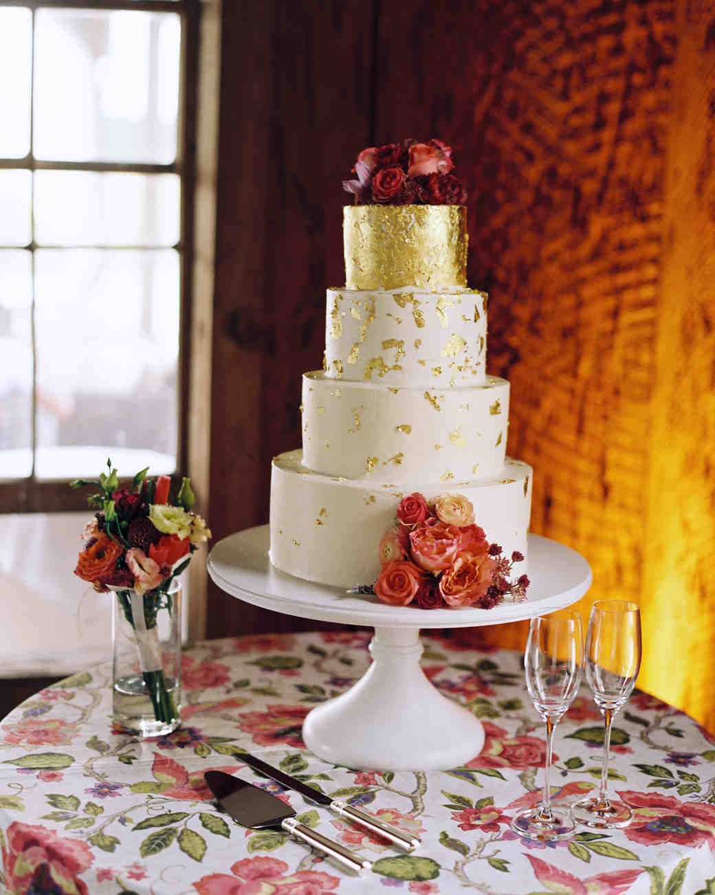 wedding cake with red flowers and gold flecks