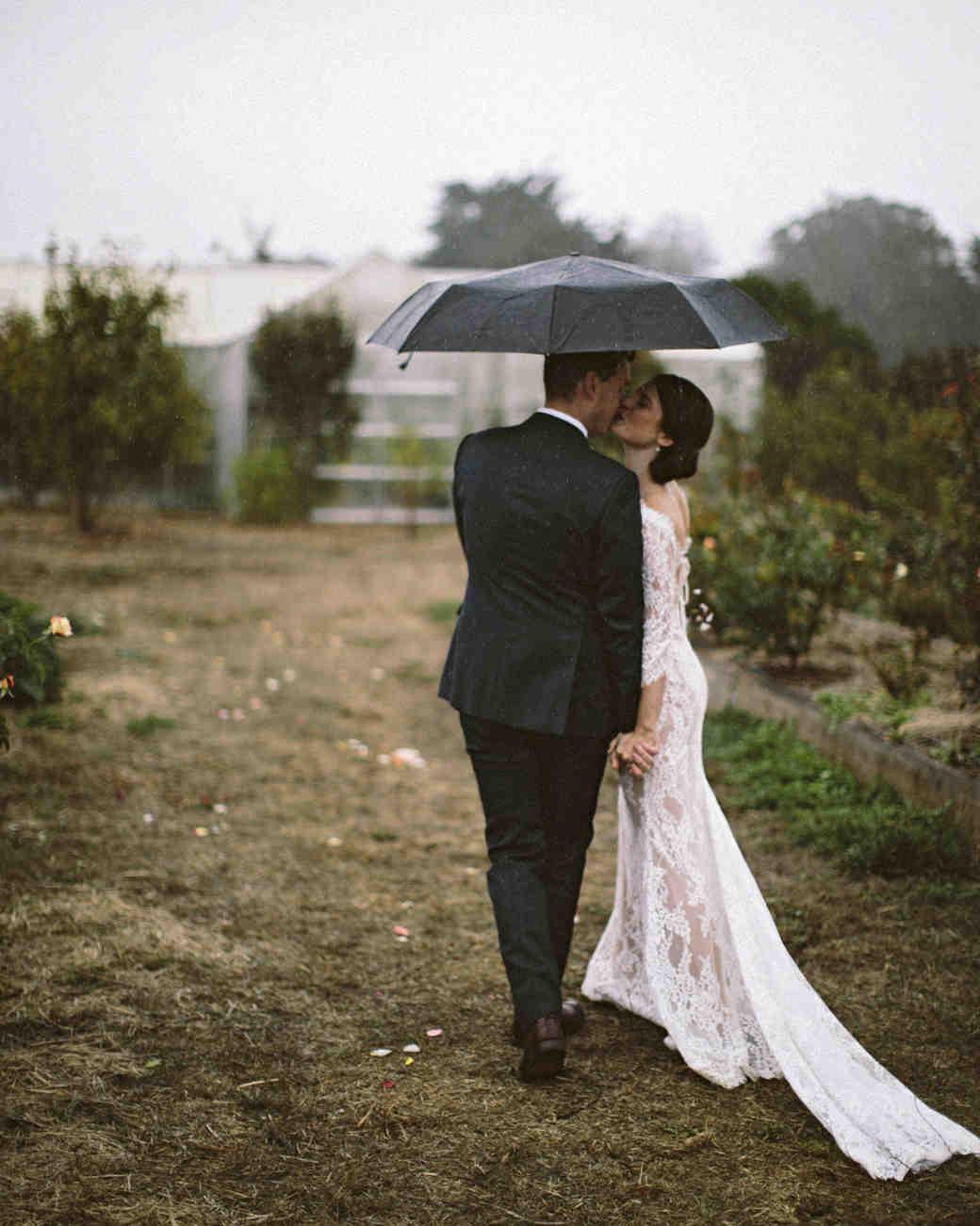 rainy wedding bride and groom kissing with umbrella