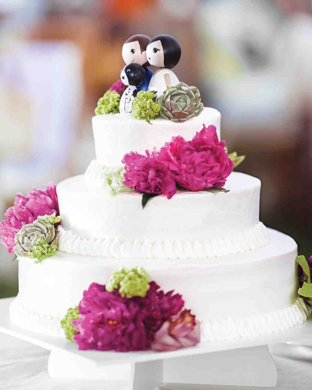 Three-Tiered White Wedding Cake with Fresh Flowers and Custom Kokeshi Dolls