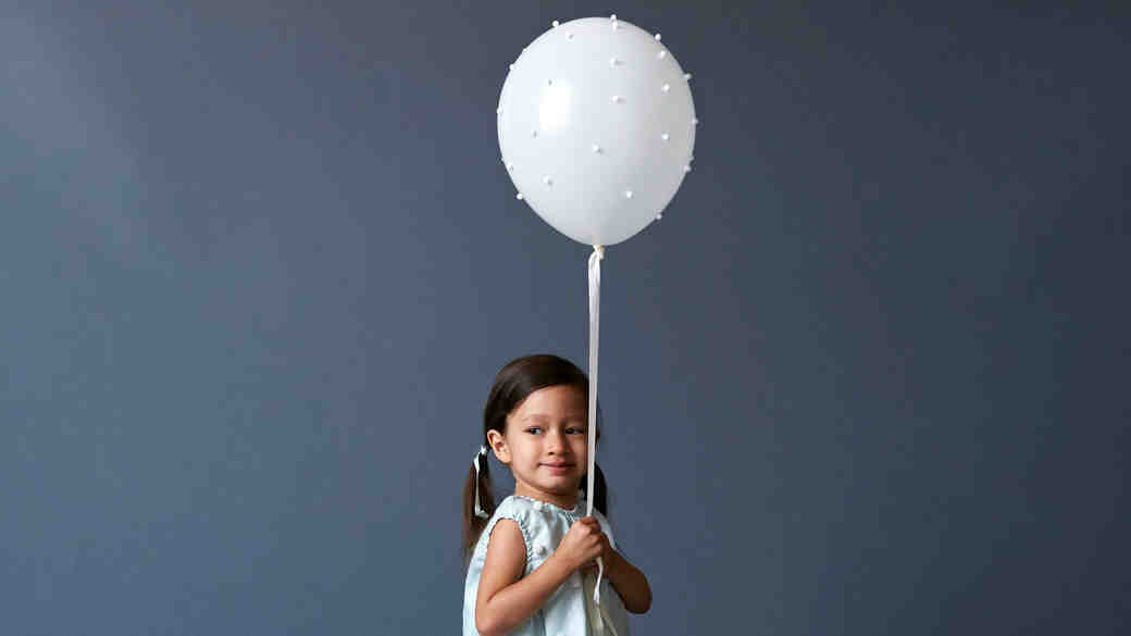 kid with pom pom balloon opener