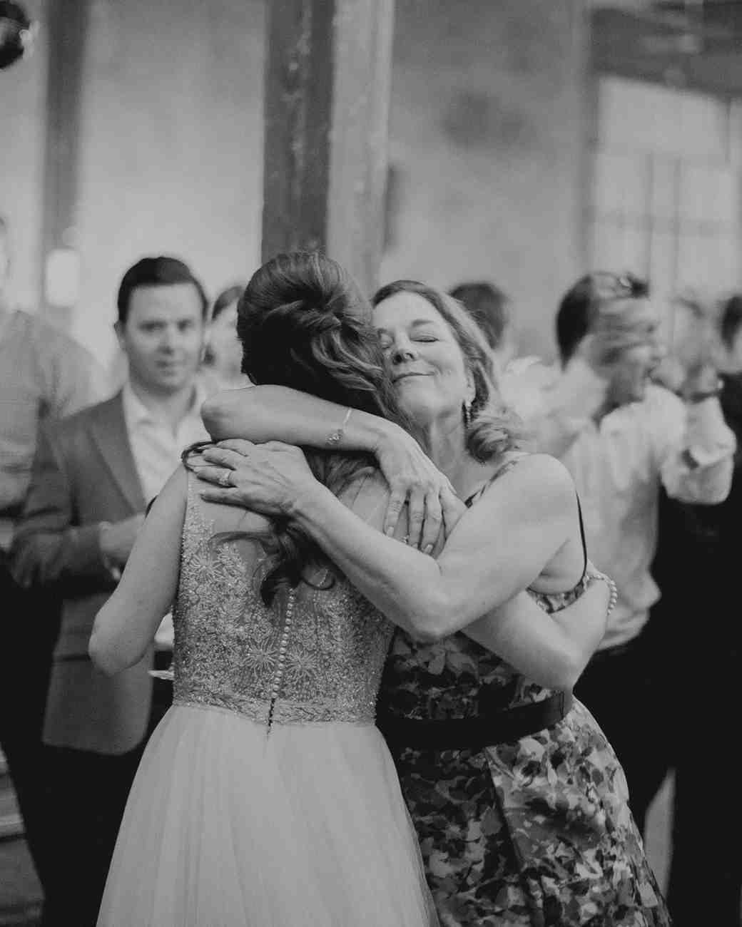 A Bride and Her Mom Hugging at the Reception