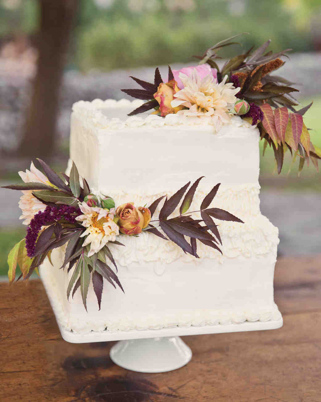 Two-Tiered Square White Wedding Cake with Pistachio Foliage and Dahlias