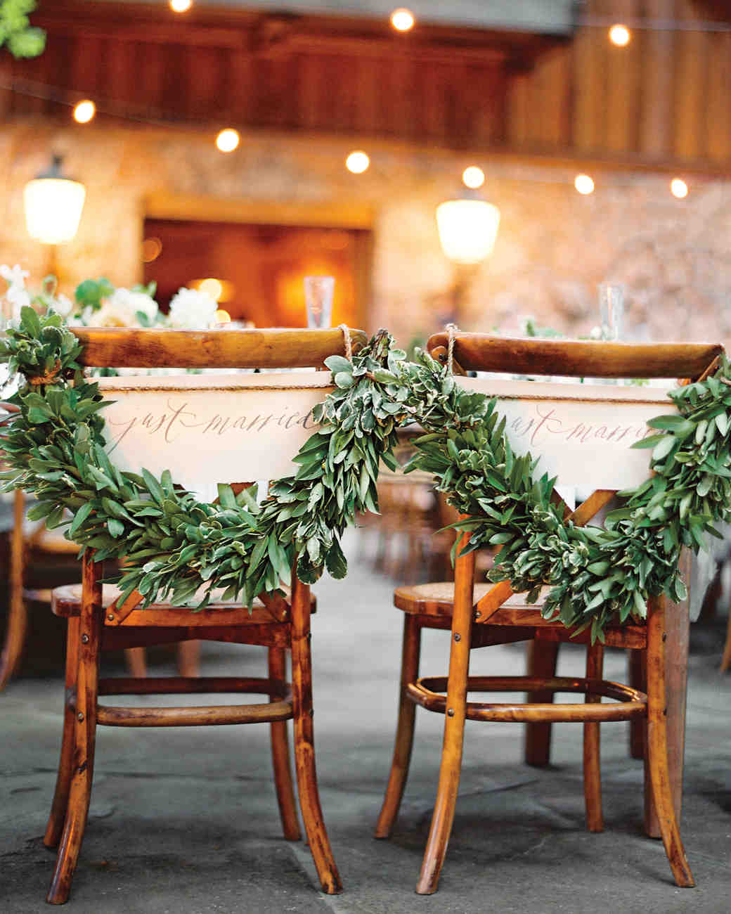 """Just Married"" Signs with Garlands on Couple's Chairs"