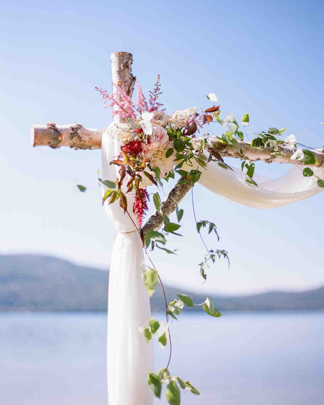 Rustic Wedding Arch with Red and Pink Flowers and White Fabric