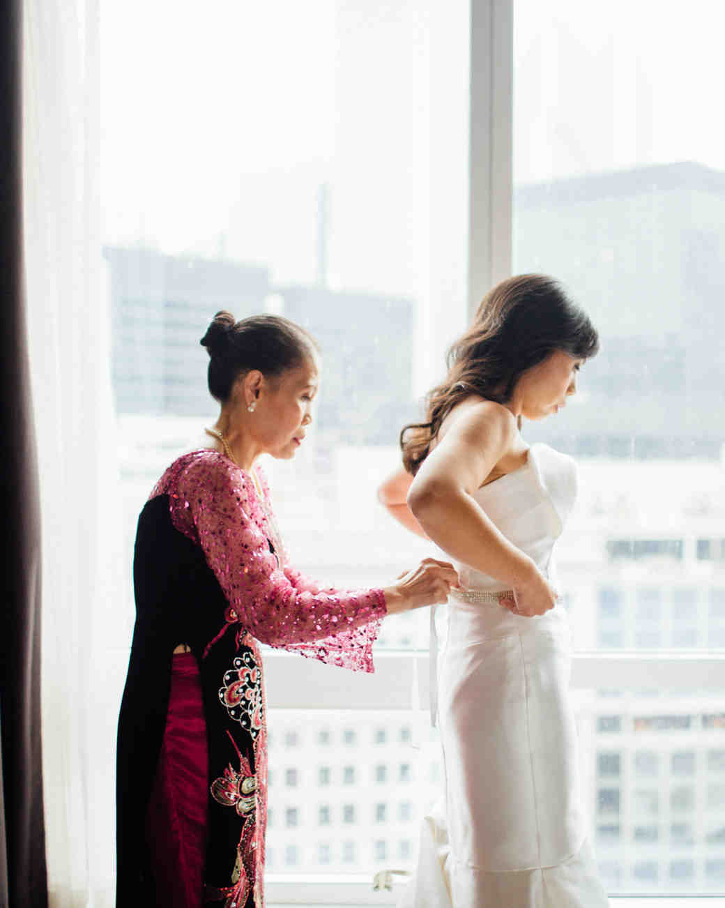 A Mother Zipping Up Her Daughter's Wedding Dress