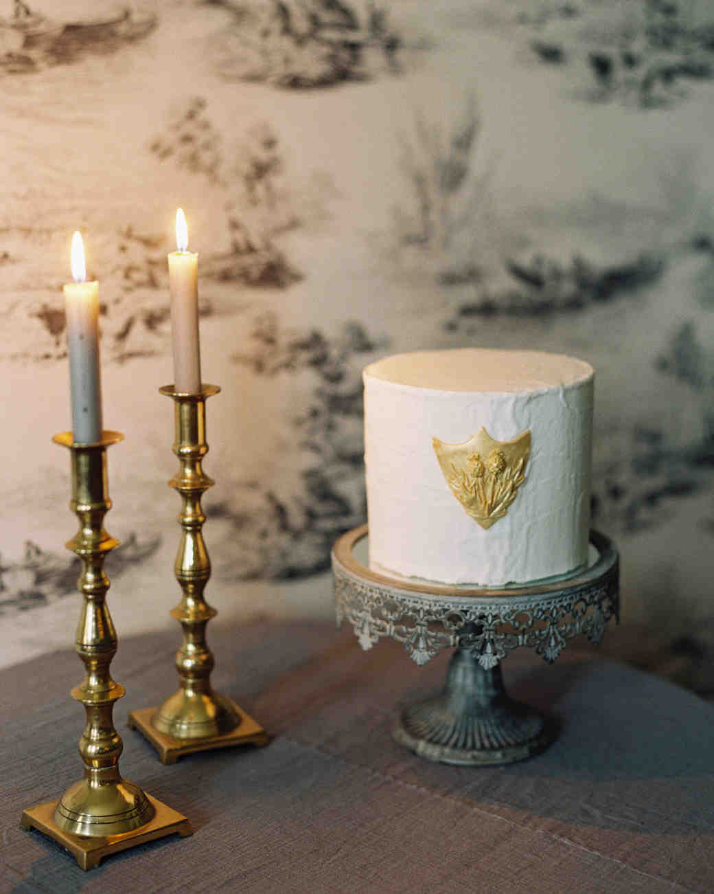 small wedding cake with gold crest