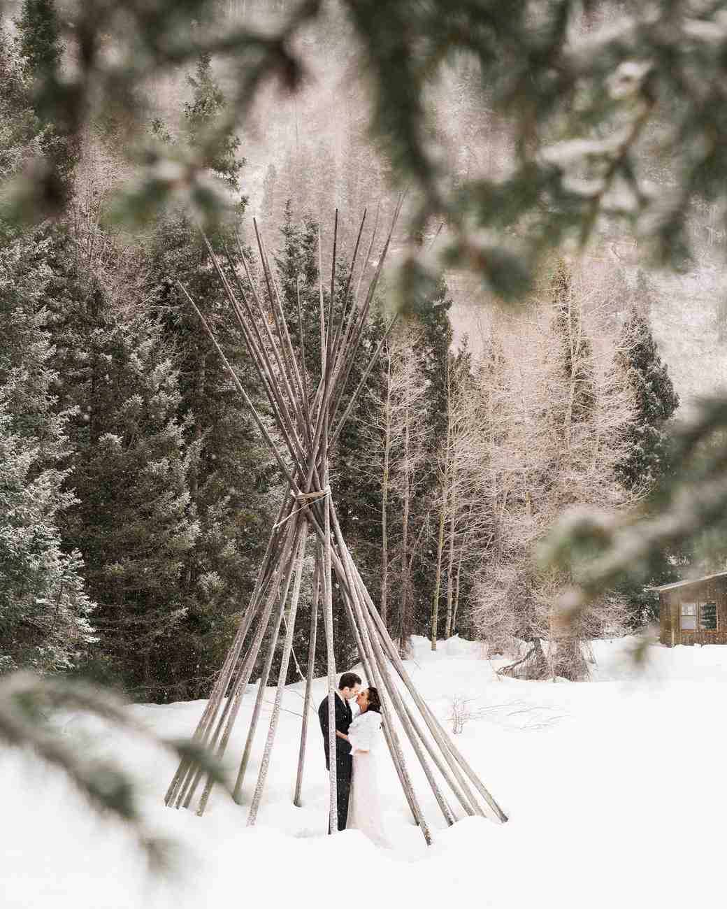 Couple Kissing in Snow Under Wooden Structure