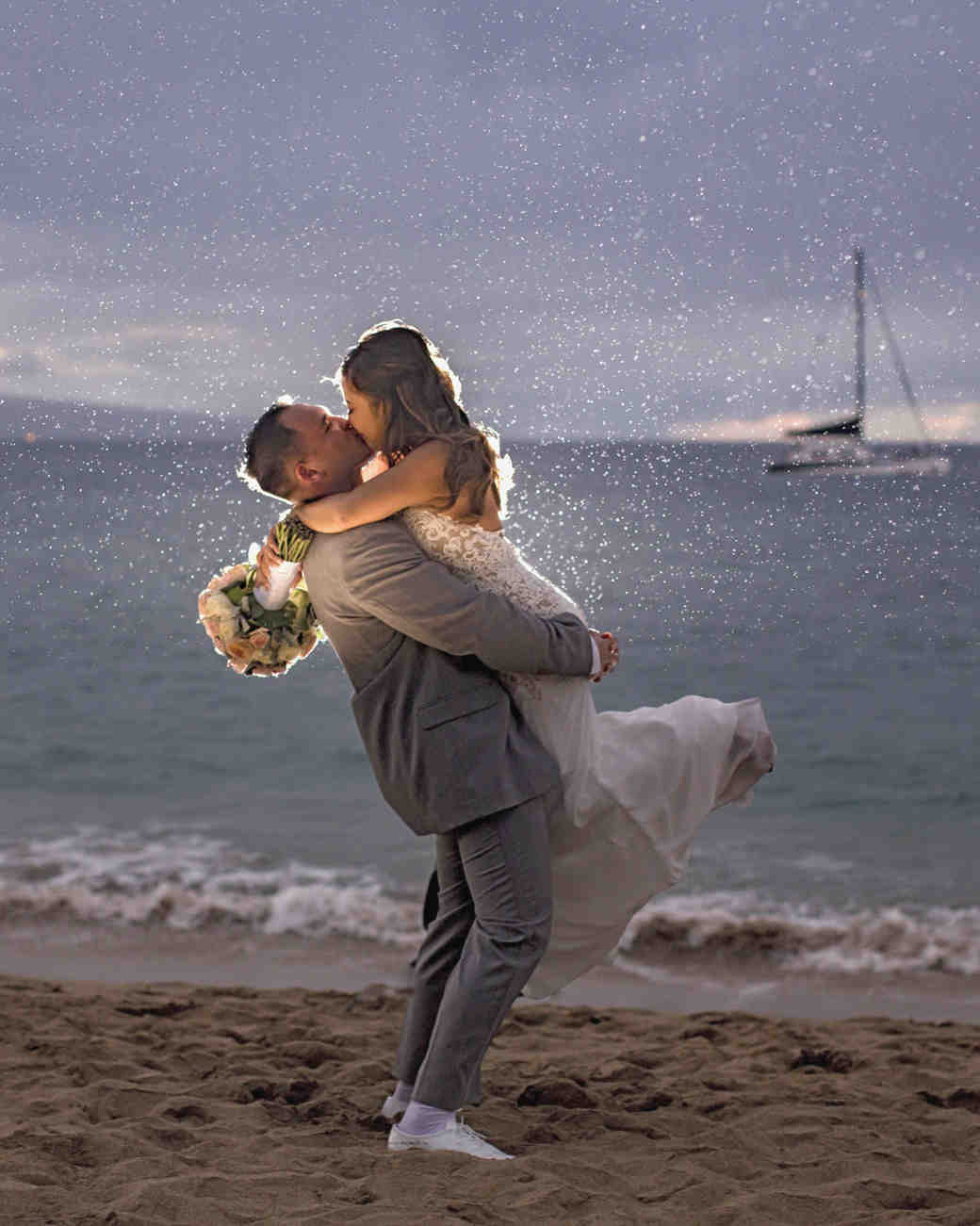 rainy wedding couple kissing on beach
