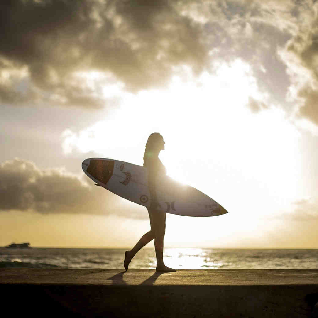 carissa moore pro surfer walking on the beach in hawaii holding her surfboard