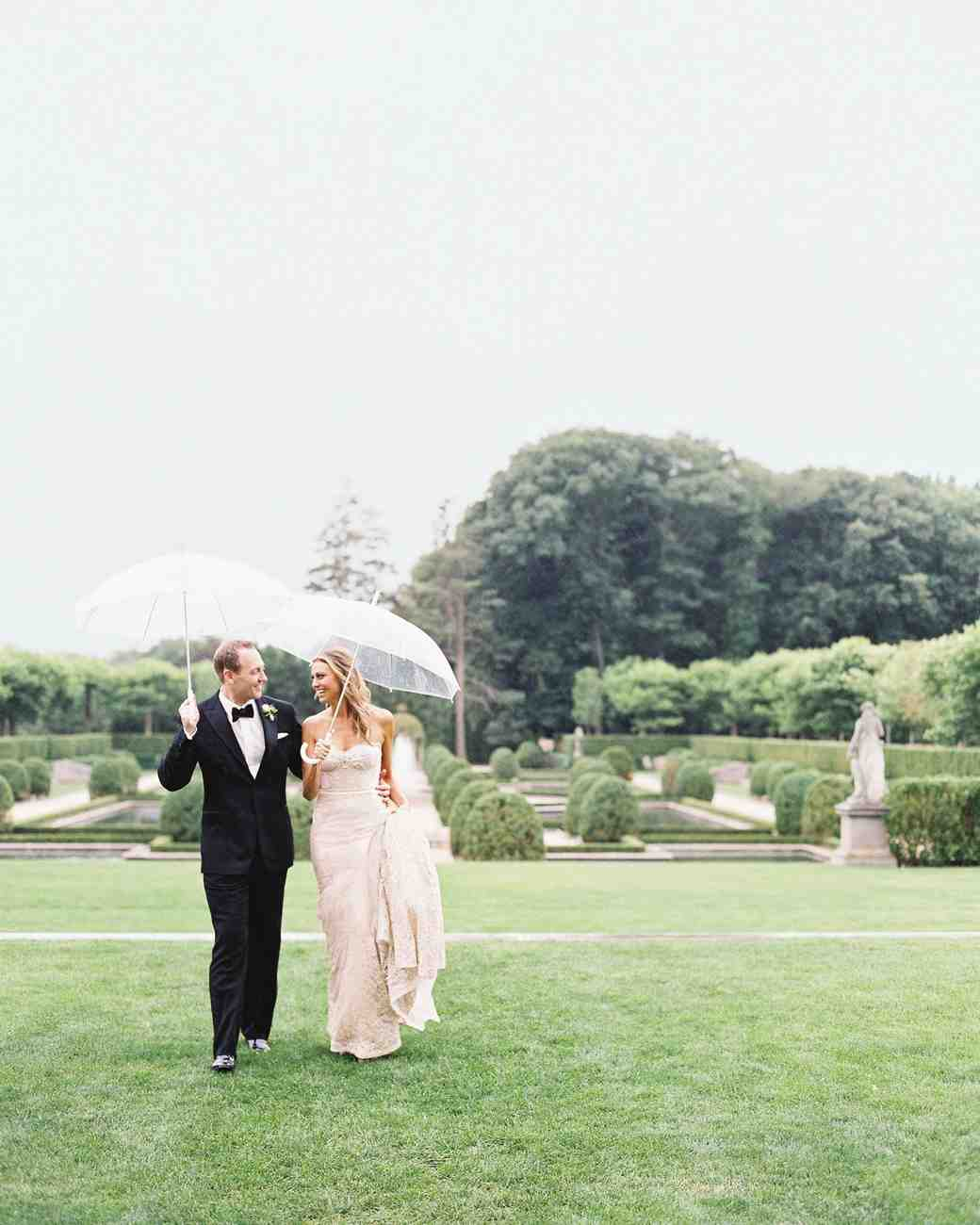newlywed couple walking in rain