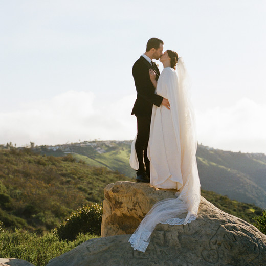 couple kissing on large rock