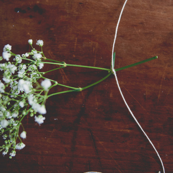 claire-thomas-bridal-shower-garden-diy-tying-string-around-flowers3-0814.jpg