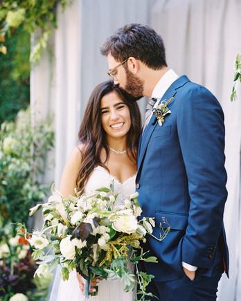 groom kissing happy bride on head