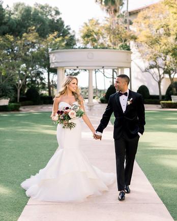 wedding couple walking through garden hand in hand