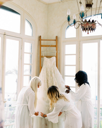 bridesmaids gathered around hanging wedding dress ball gown