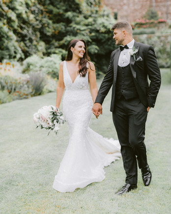 wedding couple smiling and walking together on manicured lawn