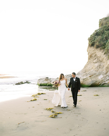 wedding couple walking on the beach hand in hand