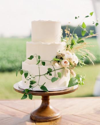 three tier wedding cake displayed on wood table