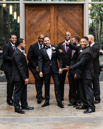 groom standing with groomsmen wearing black tuxedos