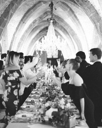 adrienne cameron wedding guests raising a toast in crypt
