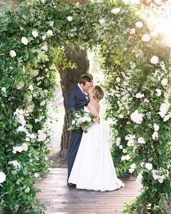 amanda will wedding couple kiss under floral arch