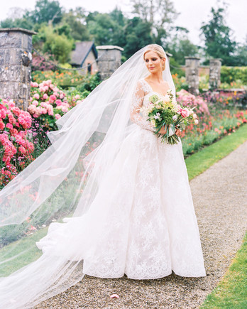 bride wearing a lace long sleeve sweetheart neckline Monique Lhuillier lace ball gown with long veil
