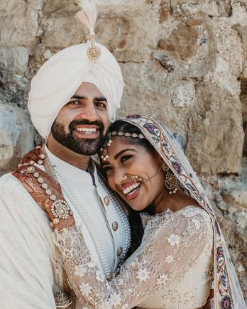 indian wedding bride holding groom smiling