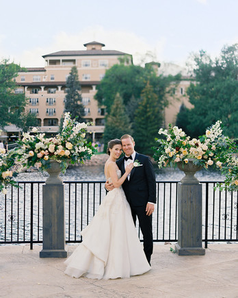 couple posing on terrace between floral urns in front of water