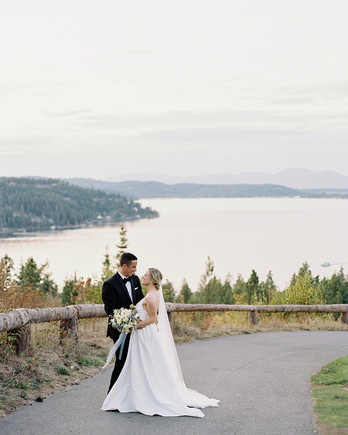 bride and groom smile standing on paved pathway outside