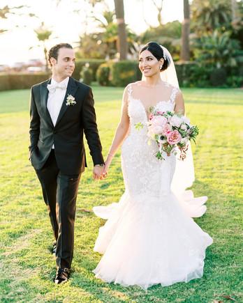wedding couple walking across lawn together