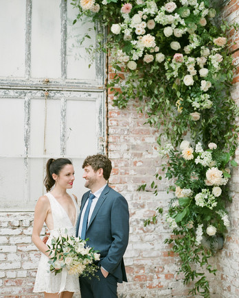 Wedding couple standing in front of brick wall with flowers