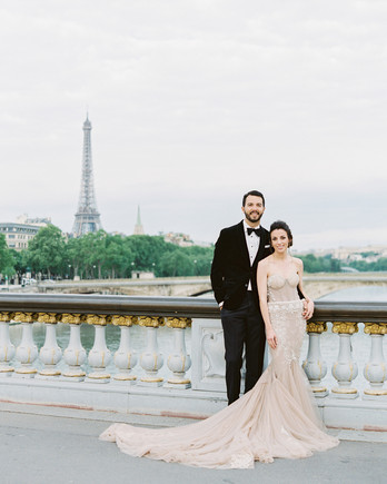 bride and groom posing on bride in front of eiffel tower