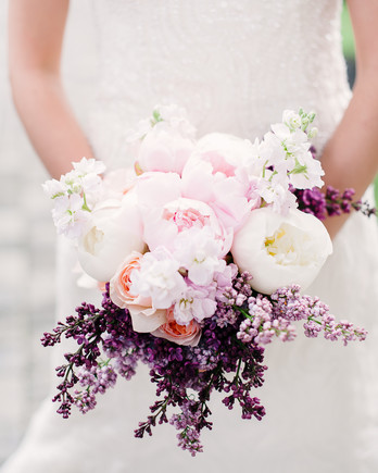bride holding pink white purple floral bouquet
