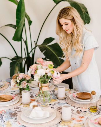 woman setting flowers at table for brunch