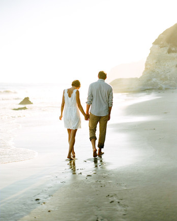 couple holding hands on beach outdoor engagement photos