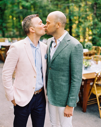 grooms kissing at welcome party