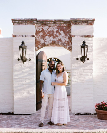 bride and groom to-be smiling outside wedding rehearsal dinner venue