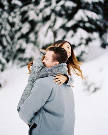man carrying woman snow