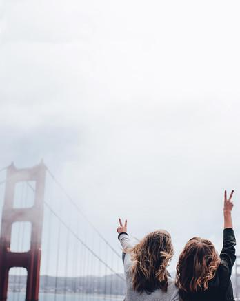 san francisco women standing in front of golden gate bridge foggy day
