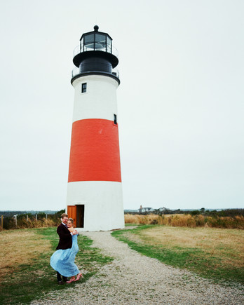 destination engagement couple red and white lighthouse